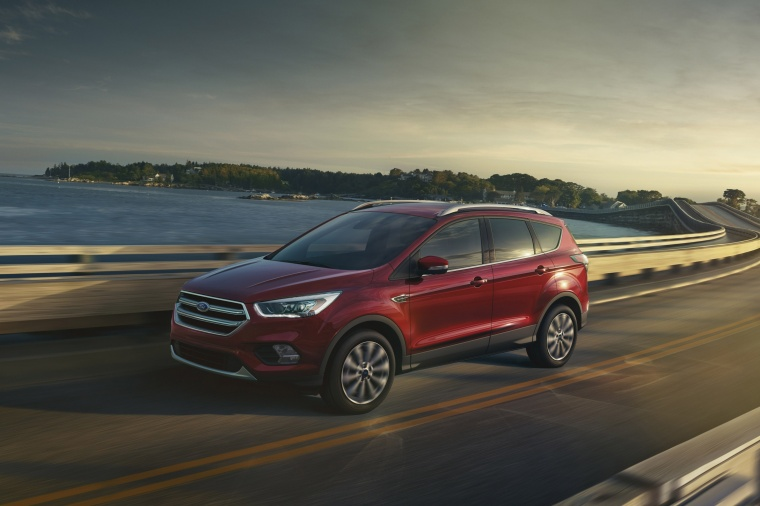 Picture of a driving 2017 Ford Escape Titanium in Ruby Red Metallic Tinted Clearcoat from a front left three-quarter perspective
