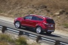 Picture of a driving 2017 Ford Escape Titanium in Ruby Red Metallic Tinted Clearcoat from a rear left three-quarter perspective