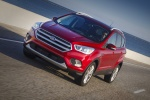 Picture of a driving 2017 Ford Escape Titanium in Ruby Red Metallic Tinted Clearcoat from a front left perspective