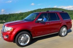 Picture of a driving 2016 Ford Expedition Platinum in Ruby Red Metallic Tinted Clearcoat from a front left three-quarter perspective