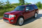 Picture of a driving 2017 Ford Expedition Platinum in Ruby Red Metallic Tinted Clearcoat from a front left perspective