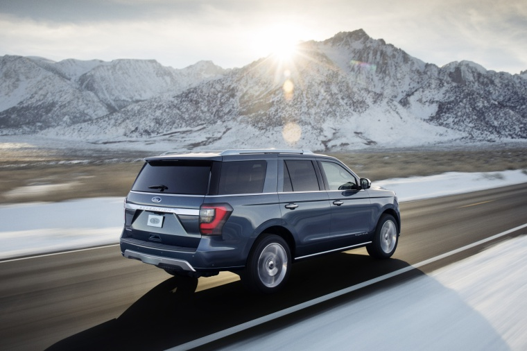 Picture of a driving 2019 Ford Expedition Platinum in Blue Metallic from a rear right three-quarter perspective
