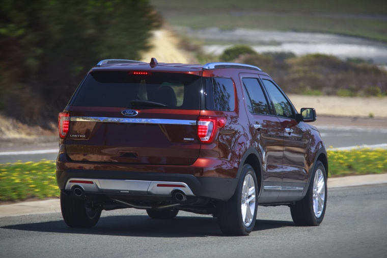 Picture of a driving 2016 Ford Explorer Limited 4WD in Bronze Fire Metallic Tinted Clearcoat from a rear right perspective