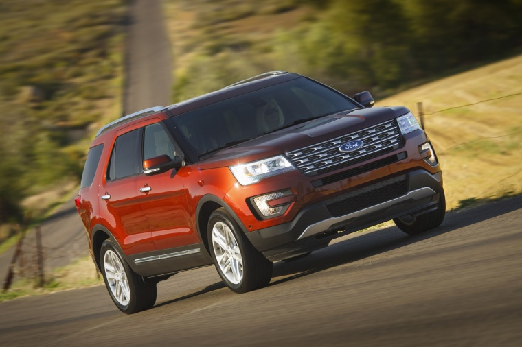 Picture of a driving 2016 Ford Explorer Limited 4WD in Bronze Fire Metallic Tinted Clearcoat from a front right three-quarter perspective