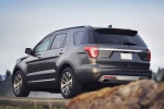 Picture of a driving 2019 Ford Explorer Platinum 4WD in Magnetic Metallic from a rear left three-quarter perspective