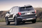 Picture of a driving 2019 Ford Explorer Platinum 4WD in Magnetic Metallic from a rear left perspective