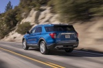 Picture of a driving 2020 Ford Explorer Limited in Atlas Blue Metallic from a rear left perspective
