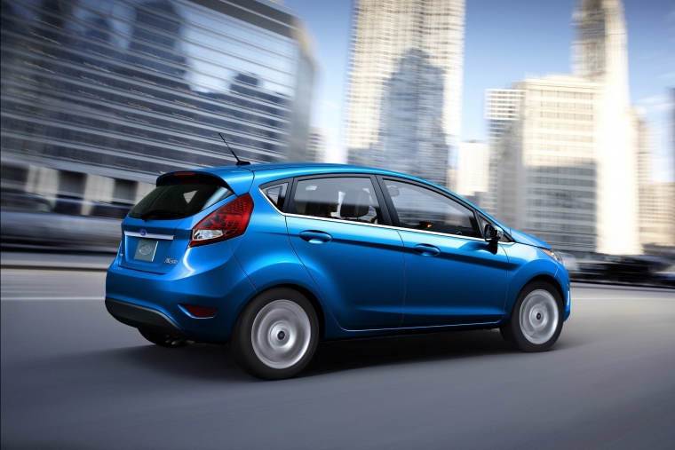 Driving 2012 Ford Fiesta Hatchback in Blue Flame Metallic from a rear right three-quarter view