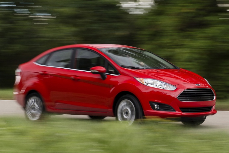 Driving 2015 Ford Fiesta Sedan Titanium in Ruby Red Metallic Tinted Clearcoat from a front right three-quarter view