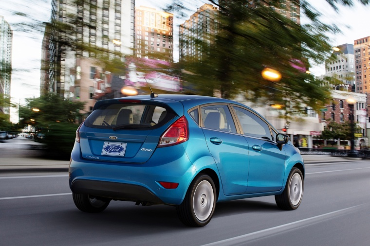 Driving 2015 Ford Fiesta Hatchback Titanium in Blue Candy Metallic Tinted Clearcoat from a rear right view