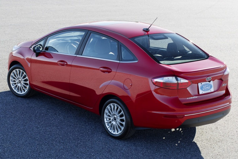 2015 Ford Fiesta Sedan Titanium in Ruby Red Metallic Tinted Clearcoat from a rear left view