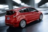 Driving 2015 Ford Fiesta Hatchback ST in Race Red from a rear right three-quarter view
