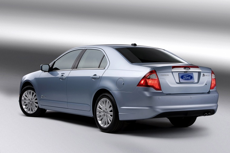 2012 Ford Fusion Hybrid in Light Ice Blue Metallic from a rear left three-quarter view