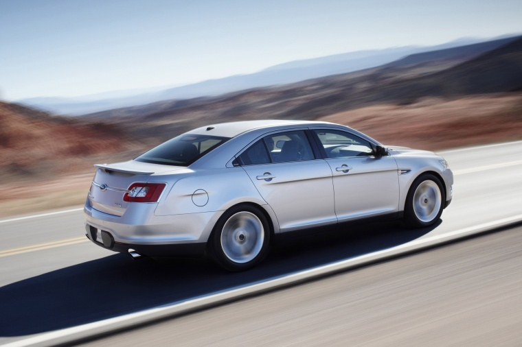Driving 2011 Ford Taurus SHO in Ingot Silver Metallic from a rear right three-quarter view