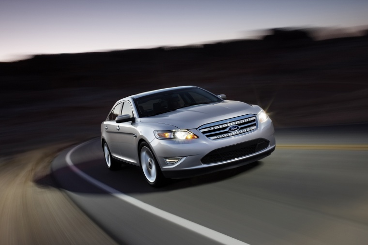 Driving 2011 Ford Taurus SHO in Ingot Silver Metallic from a front right three-quarter view