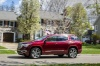 Driving 2018 GMC Acadia Denali in Crimson Red Tintcoat from a side view