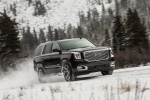 Picture of a driving 2018 GMC Yukon Denali in Onyx Black from a front right three-quarter perspective