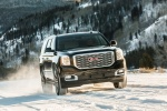 Picture of a driving 2018 GMC Yukon Denali in Onyx Black from a front right perspective
