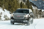 Picture of a driving 2018 GMC Yukon Denali in Onyx Black from a front left perspective
