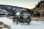 Picture of a driving 2018 GMC Yukon Denali in Onyx Black from a rear left perspective