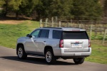 Picture of a driving 2018 GMC Yukon SLT in Quicksilver Metallic from a rear left three-quarter perspective