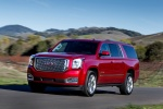 Picture of a driving 2018 GMC Yukon XL Denali in Red from a front left three-quarter perspective