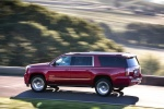 Picture of a driving 2018 GMC Yukon XL Denali in Red from a rear left three-quarter perspective