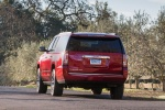 Picture of a driving 2018 GMC Yukon XL Denali in Red from a rear left perspective