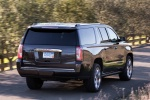 Picture of a driving 2018 GMC Yukon XL Denali in Iridium Metallic from a rear right perspective
