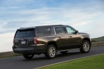 Picture of a driving 2018 GMC Yukon XL Denali in Iridium Metallic from a rear right three-quarter perspective