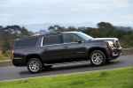 Picture of a driving 2018 GMC Yukon XL Denali in Iridium Metallic from a right side perspective
