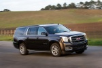 Picture of a driving 2018 GMC Yukon XL Denali in Iridium Metallic from a front right three-quarter perspective