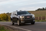 Picture of a driving 2018 GMC Yukon XL Denali in Iridium Metallic from a front right perspective