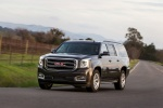 Picture of a driving 2018 GMC Yukon XL Denali in Iridium Metallic from a front left perspective