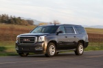 Picture of a driving 2018 GMC Yukon XL Denali in Iridium Metallic from a front left three-quarter perspective