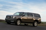 Picture of a driving 2018 GMC Yukon XL Denali in Iridium Metallic from a left side perspective