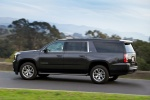 Picture of a driving 2018 GMC Yukon XL Denali in Iridium Metallic from a rear left three-quarter perspective
