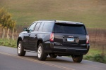 Picture of a driving 2018 GMC Yukon XL Denali in Iridium Metallic from a rear left perspective