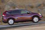 Picture of a driving 2014 Honda CR-V EX-L AWD in Basque Red Pearl II from a side perspective