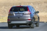 Picture of a driving 2016 Honda CR-V Touring in Modern Steel Metallic from a rear right perspective