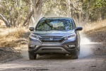 Picture of a driving 2016 Honda CR-V Touring in Modern Steel Metallic from a frontal perspective