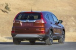 Picture of a driving 2016 Honda CR-V Touring AWD in Basque Red Pearl II from a rear right perspective