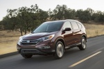 Picture of a driving 2016 Honda CR-V Touring AWD in Basque Red Pearl II from a front left three-quarter perspective