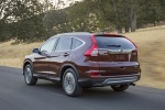 Picture of a driving 2016 Honda CR-V Touring AWD in Basque Red Pearl II from a rear left three-quarter perspective