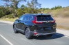 Picture of a driving 2017 Honda CR-V Touring AWD in Crystal Black Pearl from a rear left perspective