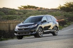 Picture of a driving 2017 Honda CR-V Touring AWD in Crystal Black Pearl from a front left three-quarter perspective