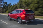 Picture of a driving 2019 Honda CR-V Touring AWD in Molten Lava Pearl from a rear left three-quarter perspective