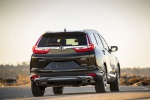Picture of a driving 2019 Honda CR-V Touring AWD in Crystal Black Pearl from a rear perspective