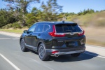 Picture of a driving 2019 Honda CR-V Touring AWD in Crystal Black Pearl from a rear left perspective