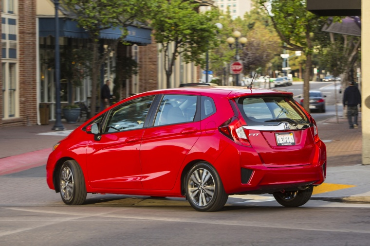 Driving 2017 Honda Fit in Milano Red from a rear left three-quarter view